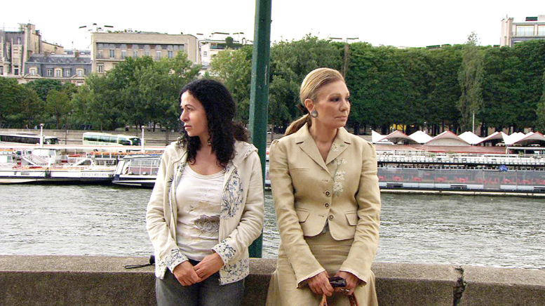 Movie Still from the Queen & I: two women sit back to back at a river