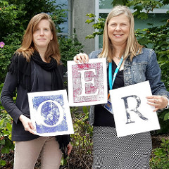 Kate Magner and Anne Tuominen holding OER sign