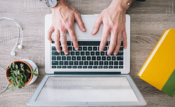 Image of hands on a laptop keyboard.