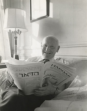Image of Isaac Bashevis Singer reading the newspaper, HaDoar