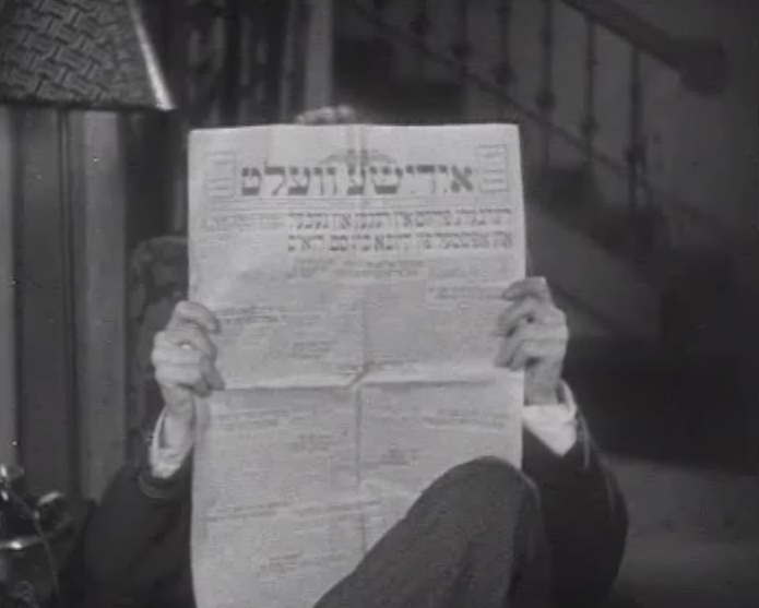 Photo of Stan Laurel reading Di Yiddische Welt