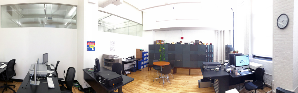 A panoramic photo of the inside of the Visual Resources Center, with desks and computers to the left, the slide shelves in the center background, and scanning equipment and desks to the right.