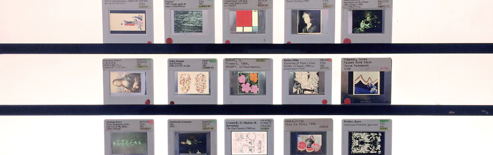 Image of fifteen 35mm slides of artworks, in three rows of five, illuminated and displayed in a light box.