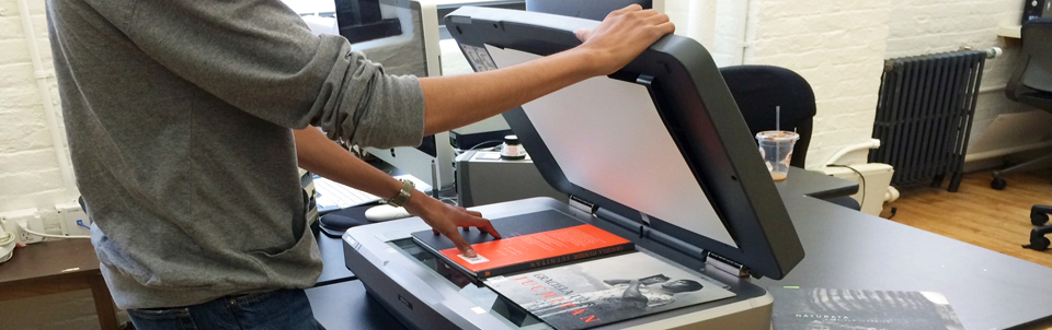 A cropped image of a student worker scanning a book.