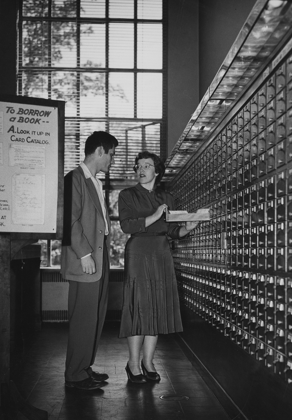 Librarian helps student navigate card catalog, 1940s.