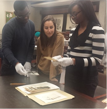 3 students inspect a folder of documents together; female student to the far right immersed in the document she is holding