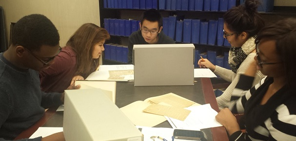 Group of students at table, poring over boxes of documents in intimate setting