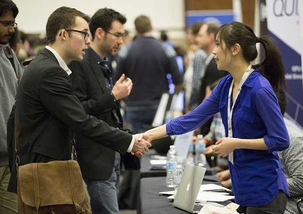 Student in suit shaking hands with woman in blue blouse at a student expo