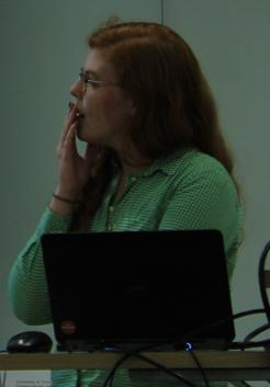 Presenter at student journal forum, contemplating as she refers to the projection screen