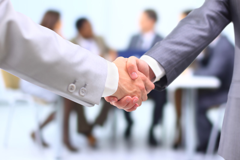 An image of two people in suits shaking hands