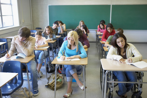 students in a classroom writing a test