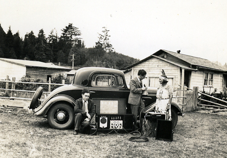 Melville Jacobs next to car interviewing a Native American woman