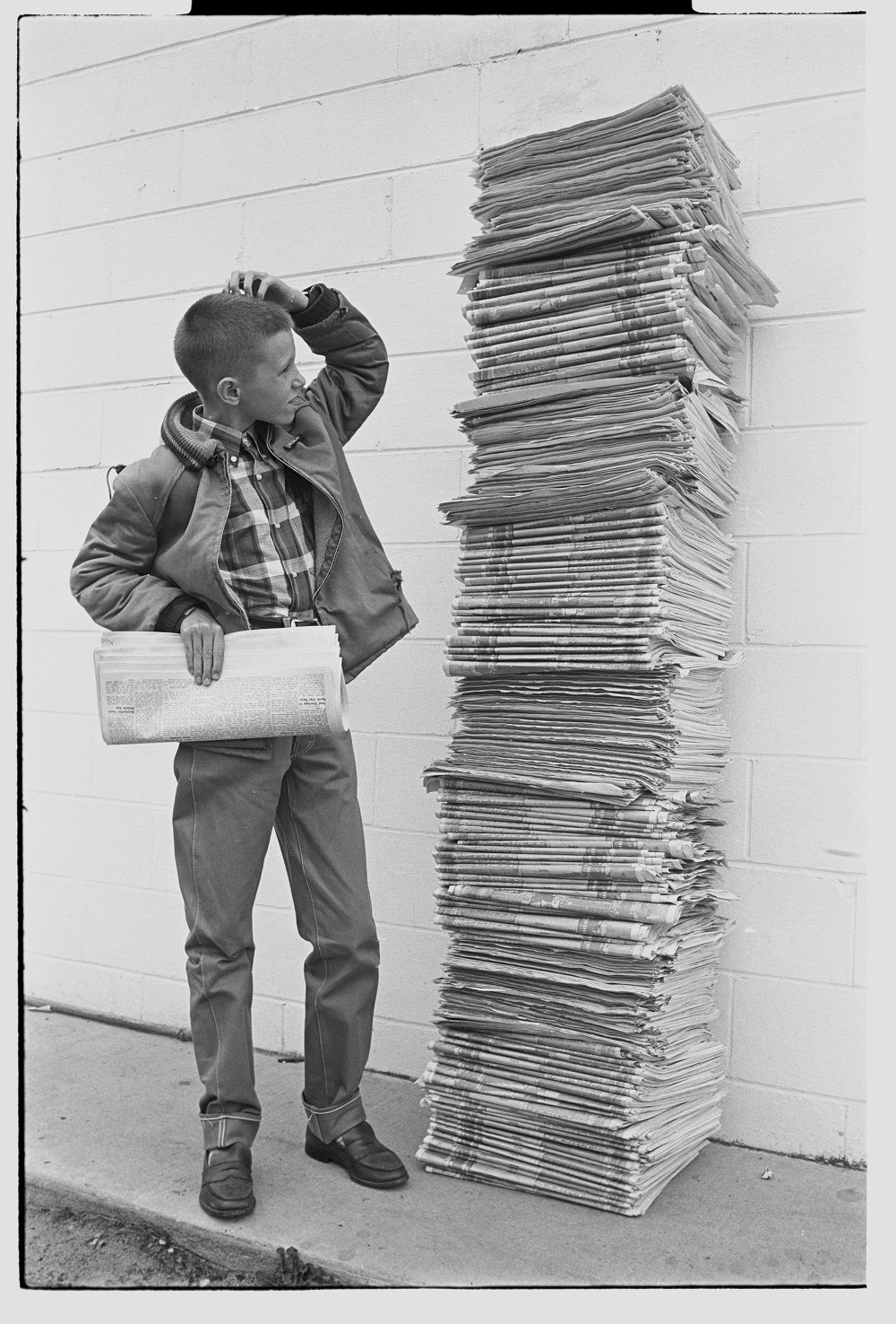 Image of a boy next to a stack of newspapers that towers over him