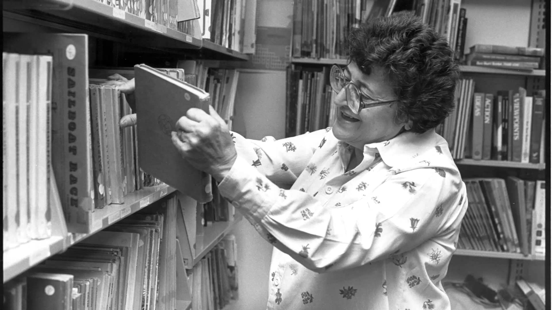 Black and white photograph of Jeanne Chall browsing books on a shelf.