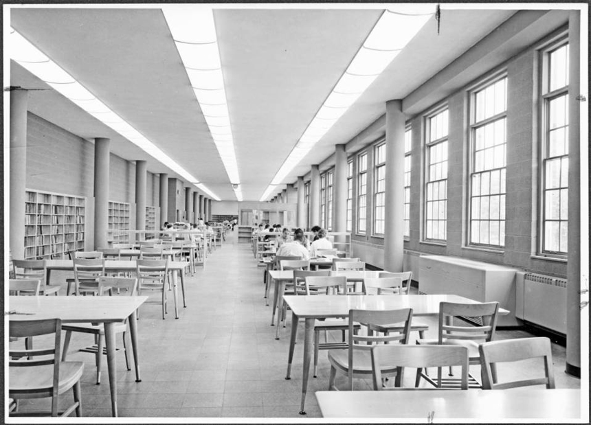 A picture which shows the length of interior of McCracken Hall's Education Library with a few adult students.   McCracken Hall was named for Thomas McCracken, Dean of the College of Education, 1922-1946. It is located on East Union Street, just west of Putnam Hall and across from Jefferson Hall. It continues to house the College of Education. Image from Ohio University Libraries, Mahn Center for Archives and Special Collections