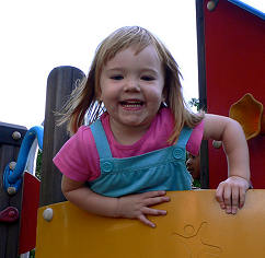 Smiling child leaning over play structure