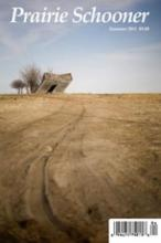 Prairie Schooner literary magazine showing barren field with old building tilted against gray blue sky