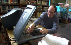 Man in glasses digitizing documents using a flatbed scanner.