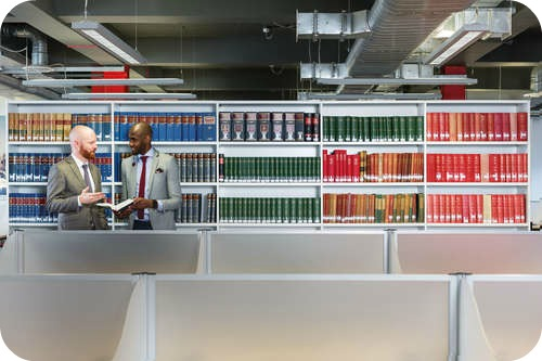 Two members of staff accessing and discussing a book in the law library