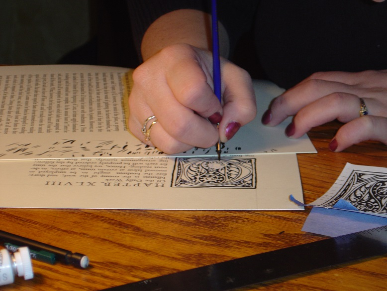 Close up of student's hands drawing a decorative initial cap.