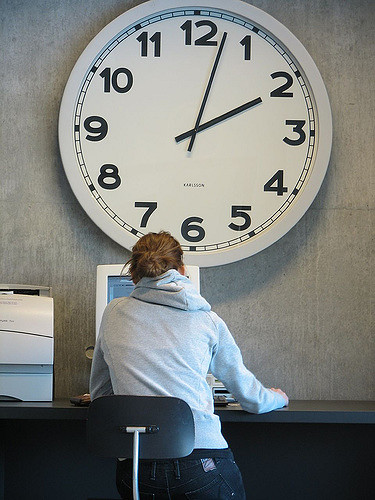 Photo of student studying in front of giant clock