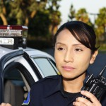 Image of corrections officer with walkie-talkie and patrol car in background