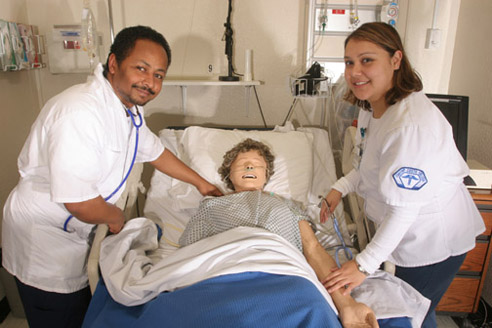 Image of two nursing students practicing with a dummy in a hospital bed.