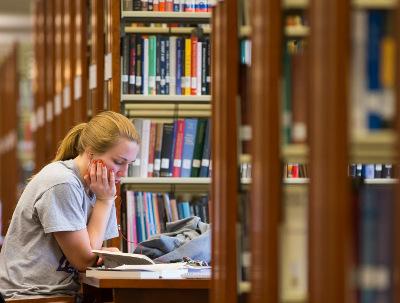 Woman studying among library books