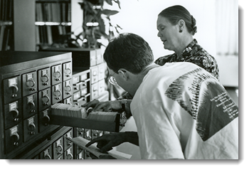 Librarian Angela Andrews using the card catalog with researcher John Miller.