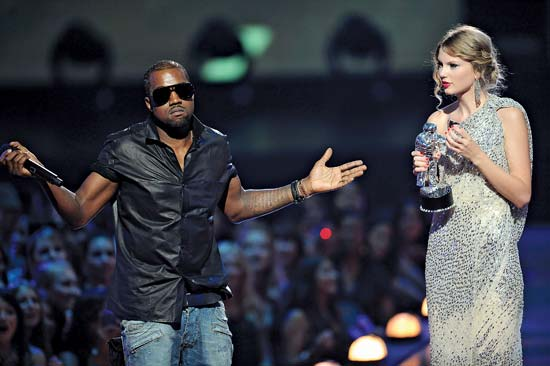 Kanye with his hands up standing in front of Taylor Swift on stage