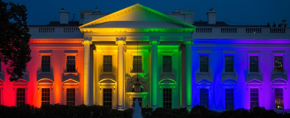 Image of the White House lit up with the LGBTQIA+ flag colors