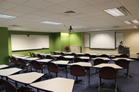 photo of classroom 1, a lecture style room with desks, a whiteboard and an instructor station