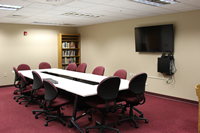 photo of faculty prep room, with six moveable tables, 12 chairs, a computer and large flat-screen display, and a bookshelf