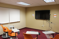 Photo of PREP room with lecturn, large-screen monitor, white board, and 4 chairs