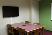photo of study room with a table, 4 chairs, large flatscreen monitor & whiteboard