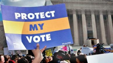"""Protesters with sign that says, """"Protect my vote."""""""