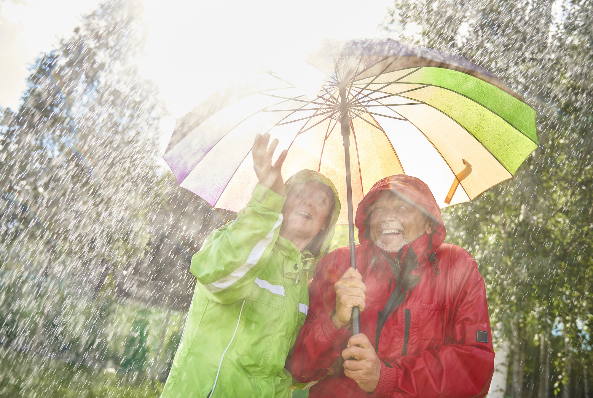 Happy couple standing with umbrella