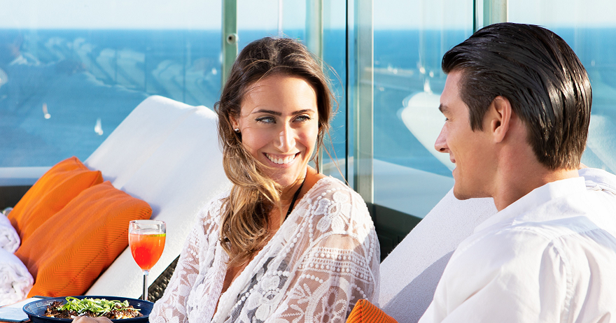 A happy couple enjoying the rooftop pool at Hotel X Toronto with lake views in the background.