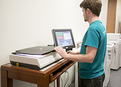 Student using flatbed scanner in the Copy and Scan Center