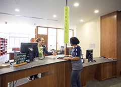 student being helped at the library Circulation Desk