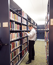 Student browsing books in the stacks