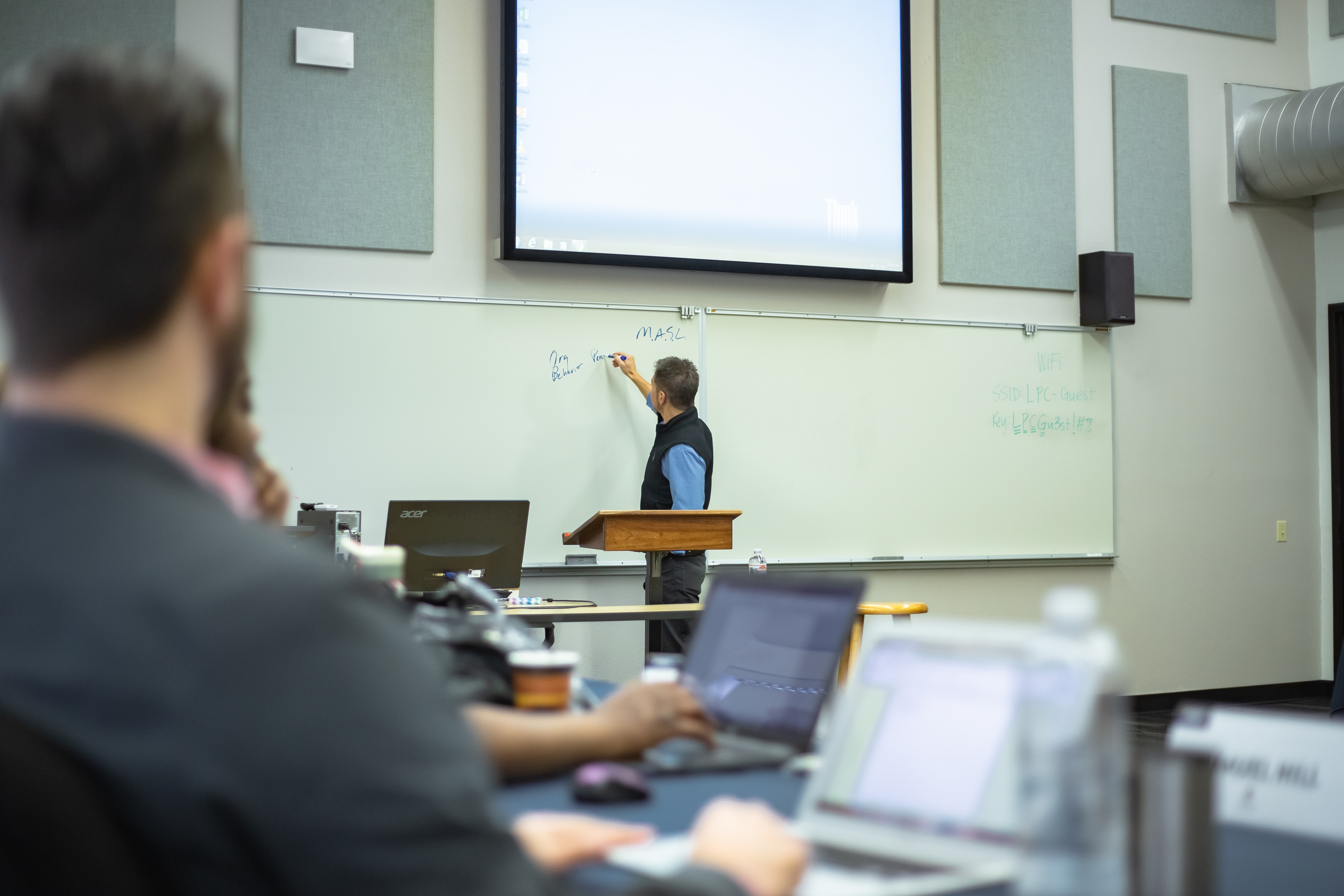 MASL Professor writing on whiteboard in front of class.