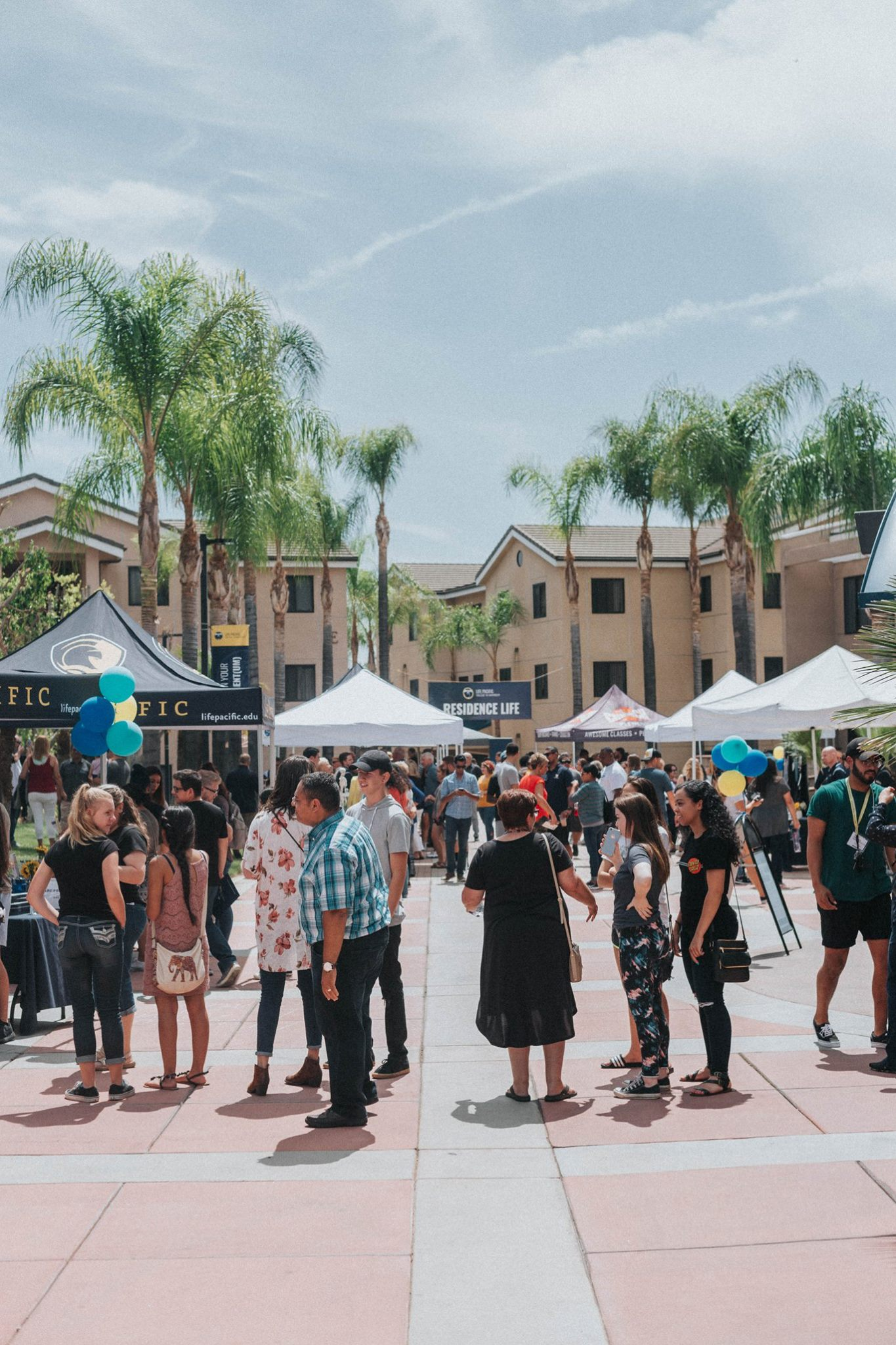 Photo of campus courtyard with students and families conversating.