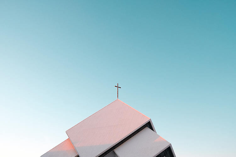 Top of church roof with cross and blue sky, church hurt