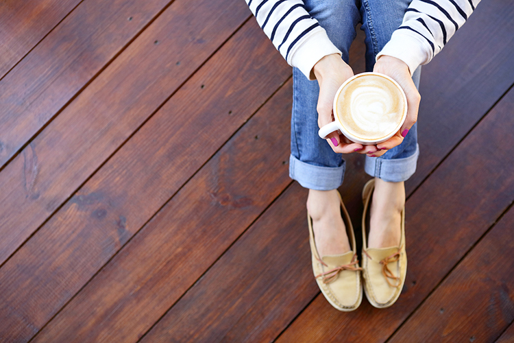 overhead shot of woman sitting on a deck, holding a cup of coffee