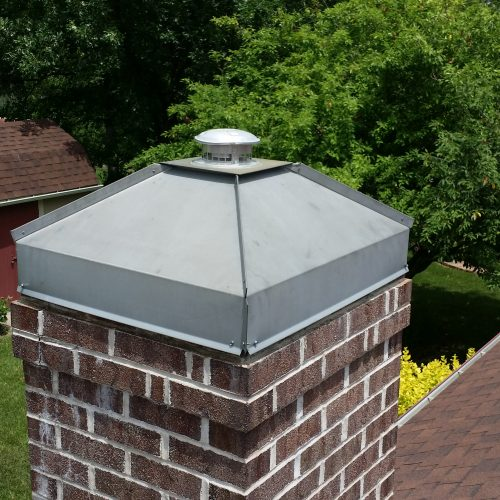 A brick chimney setting on a roof