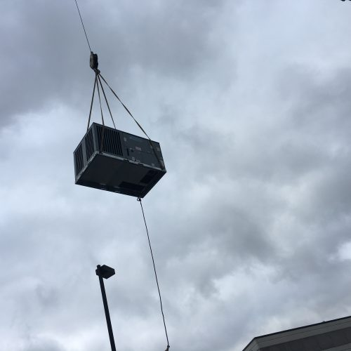 An air conditioning unit being hoisted into the air by a crane