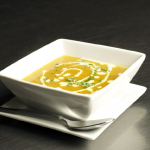 Garnished soup setting in square dish with silver spoon