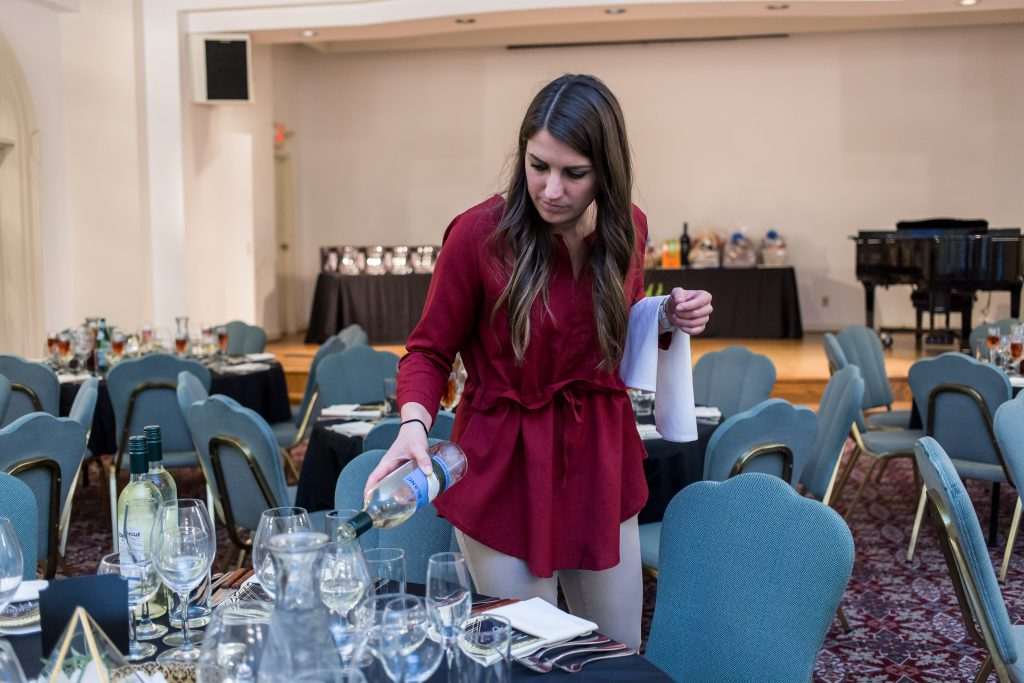 A staff member pouring wine at an event