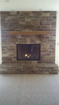 A brick fireplace with a wooden mantle